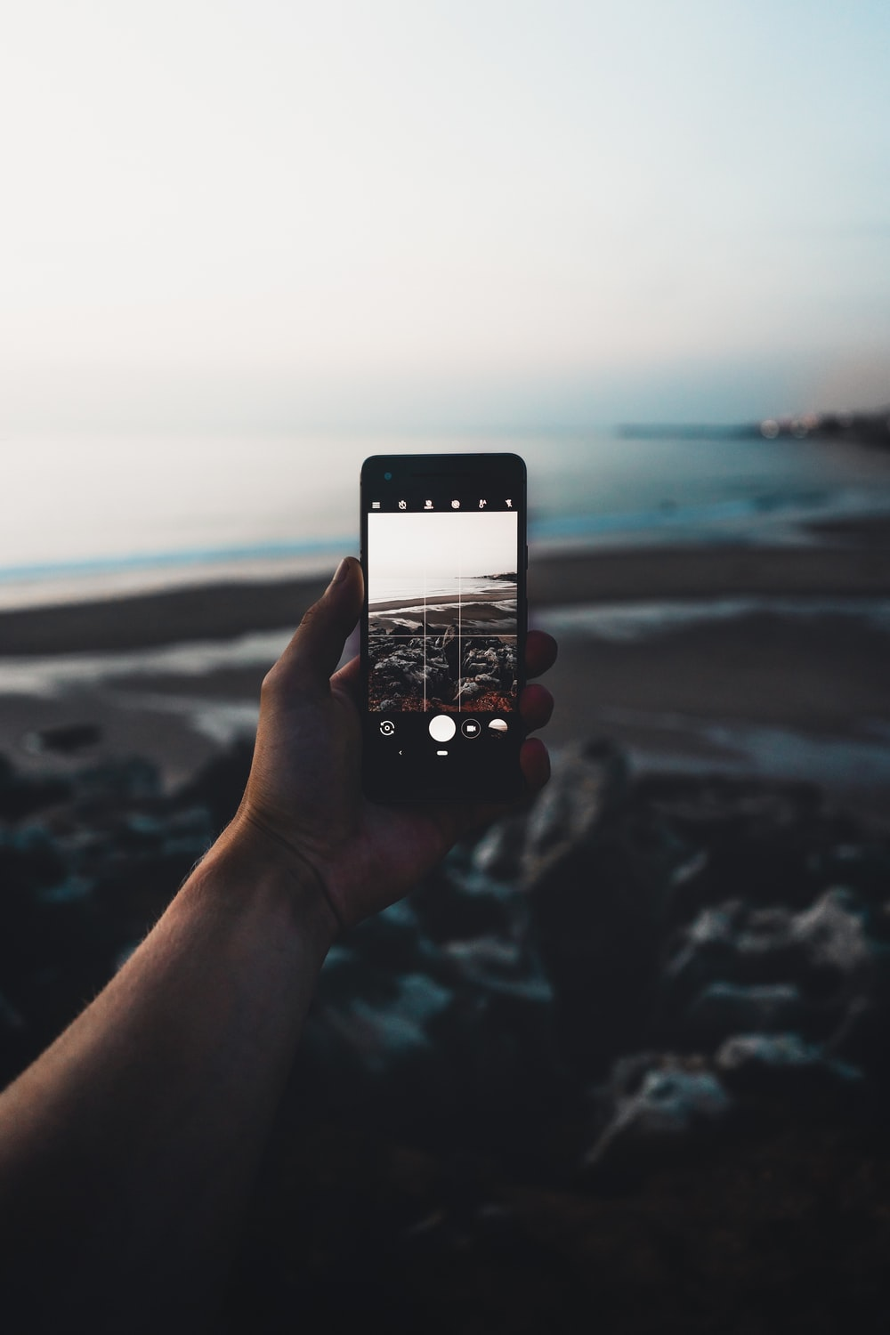 selective focus photography of person taking photo of seashore