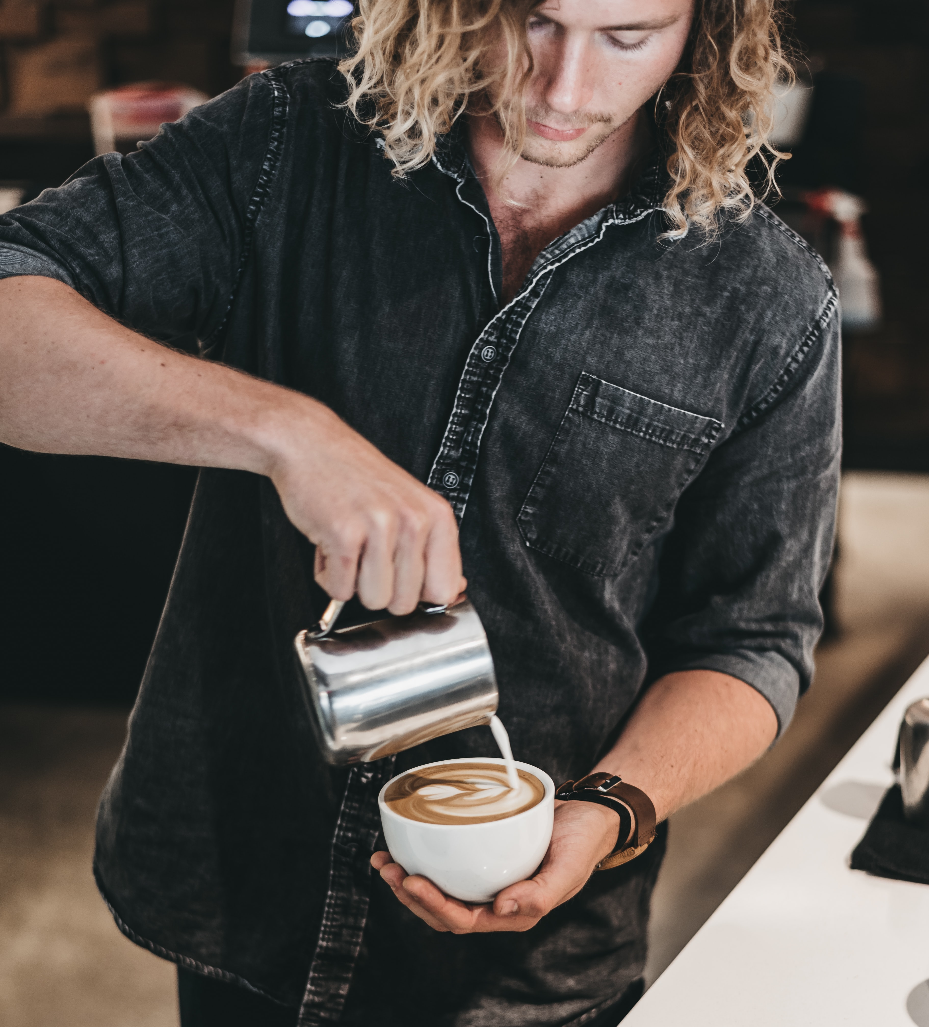 man wearing black denim jacket pouring white liquid on cup with latte art