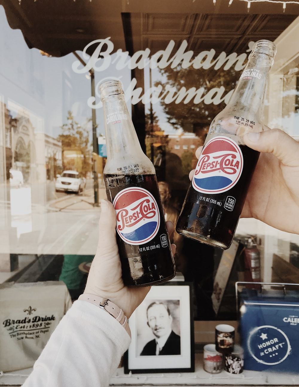 person holding Pepsi Cola soda bottles