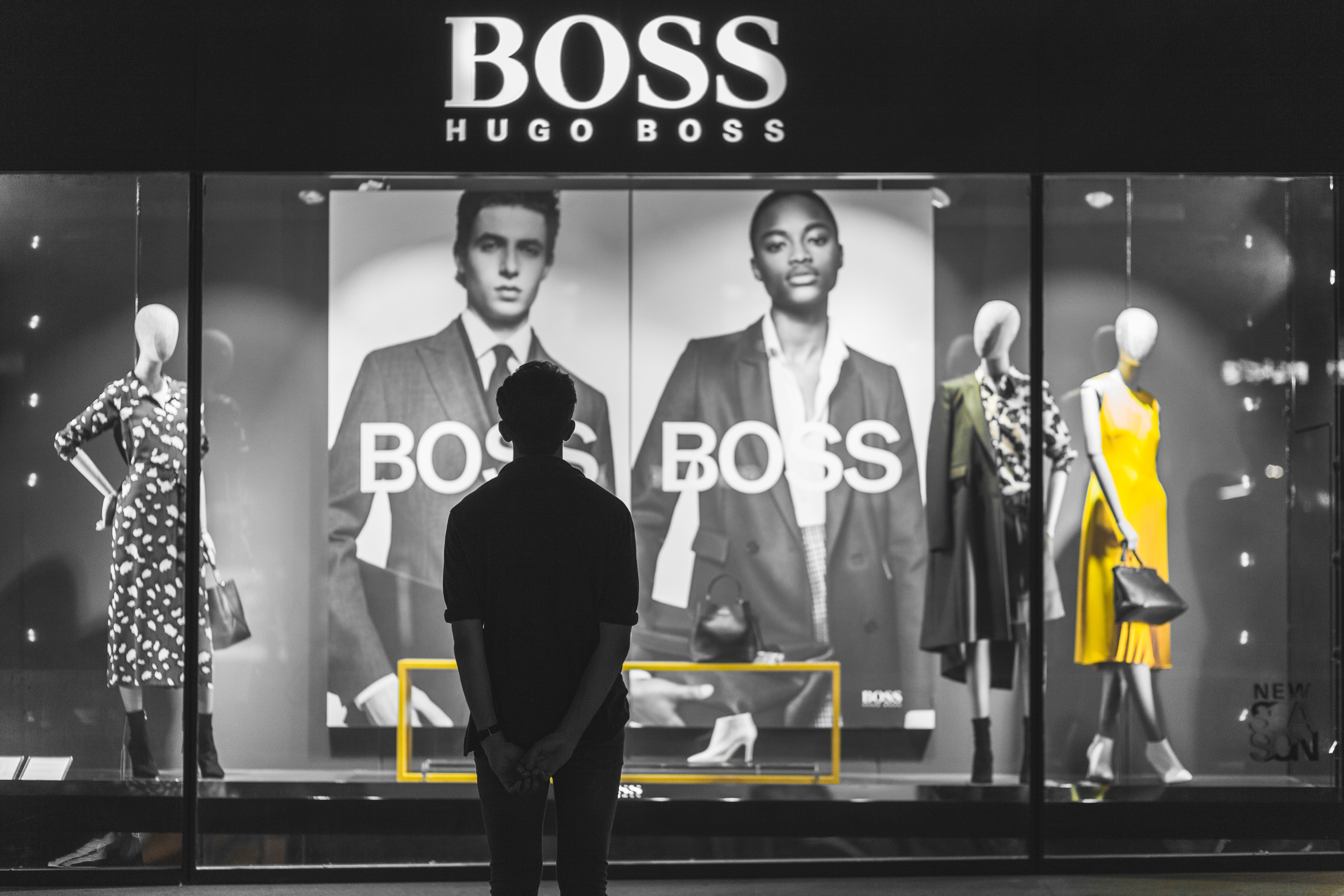 man standing in front of Boss Hugo Boss store