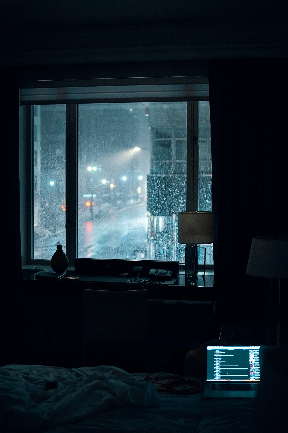 laptop computer left turned-on on bed inside room during rainy night