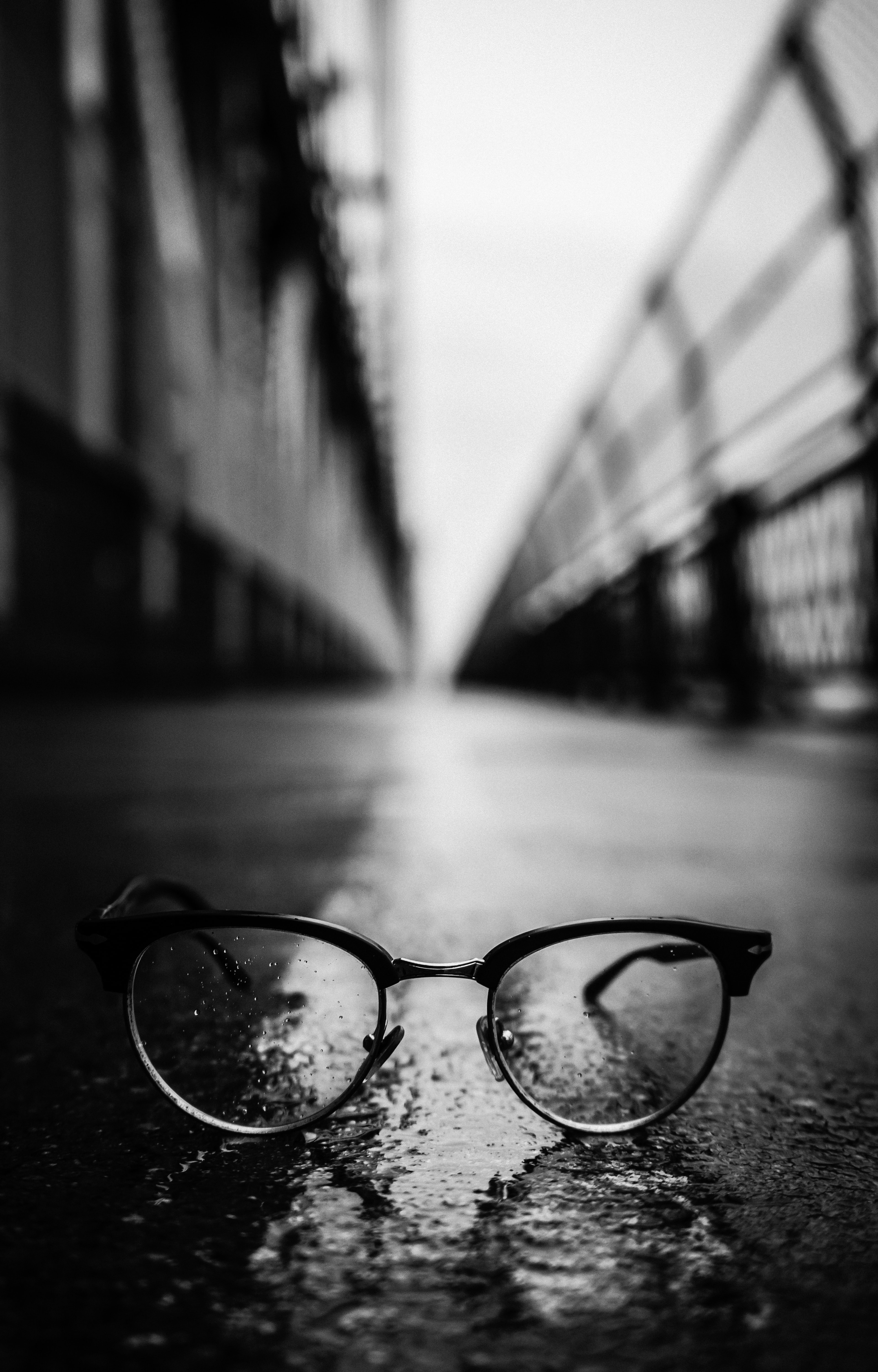 gray scale photography of Clubmaster-style sunglasses on road