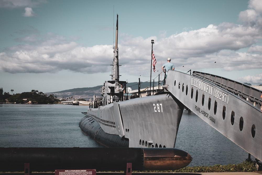 grey warship on dock during daytime