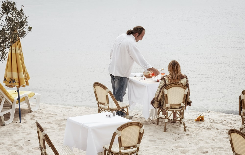 man and woman having meal at the shore