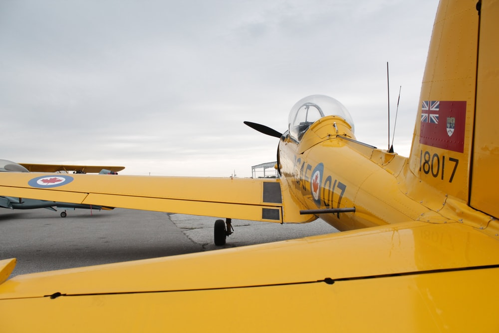 yellow airplane under cloudy sky during daytime