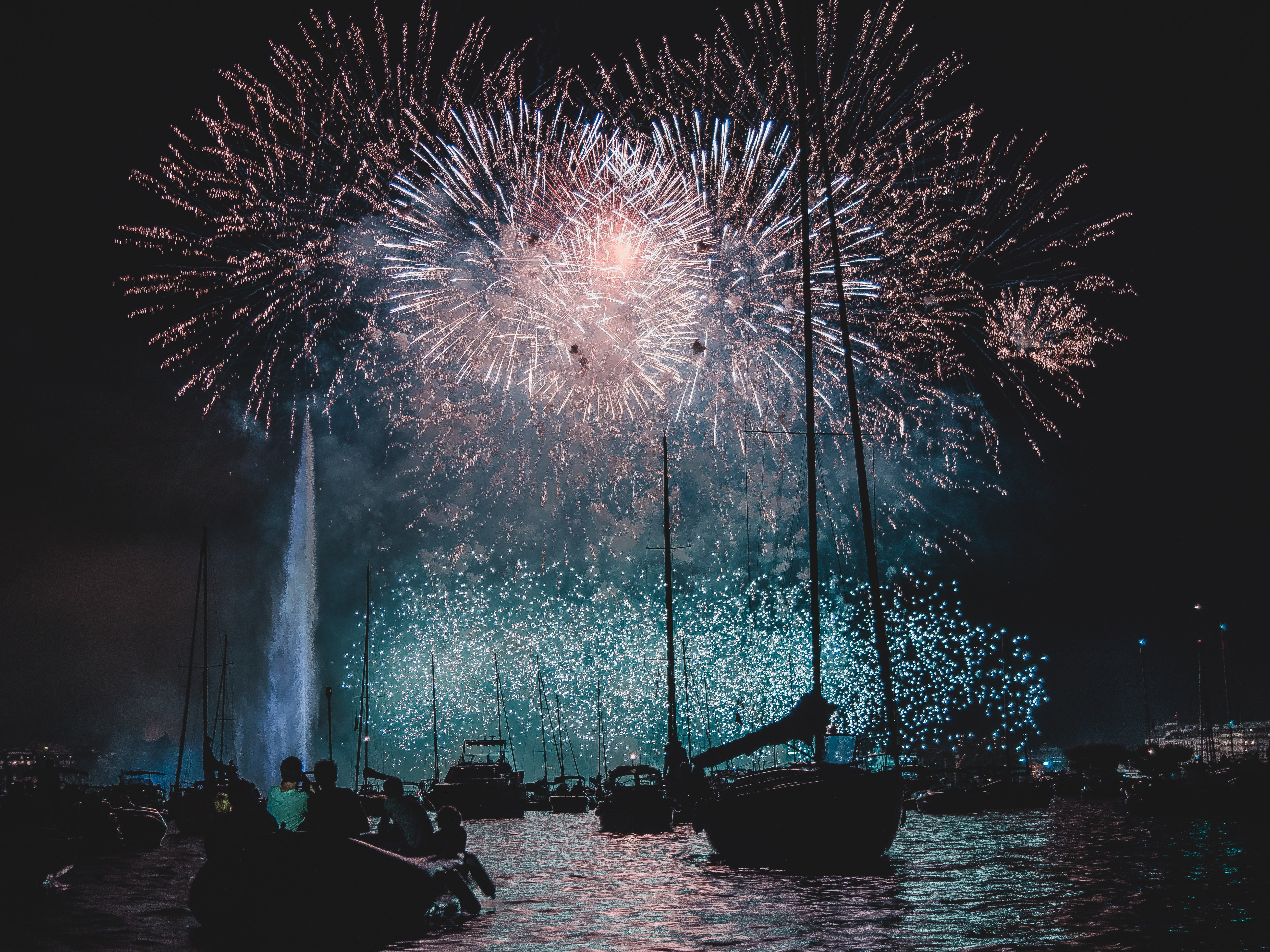 silhouette of boats under fireworks during night time