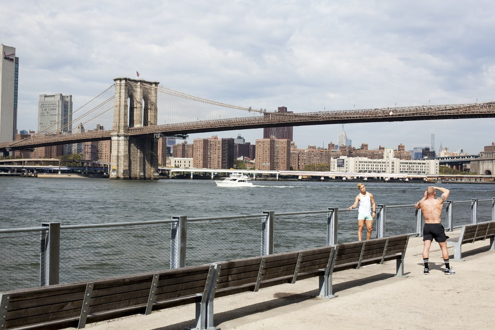two men taking picture in front of Brooklyn Bridge
