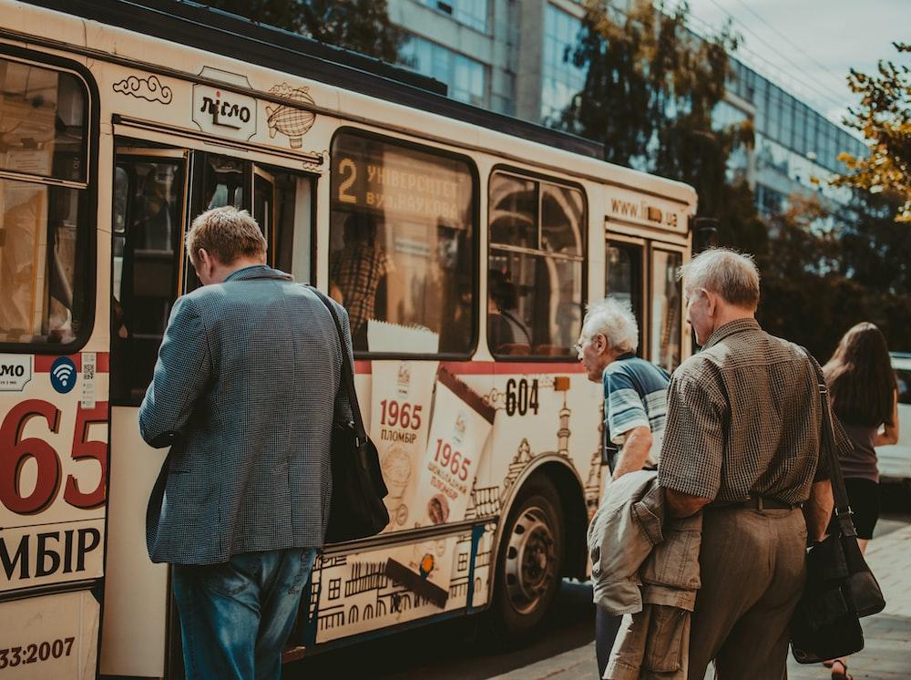 three men standing outside bus