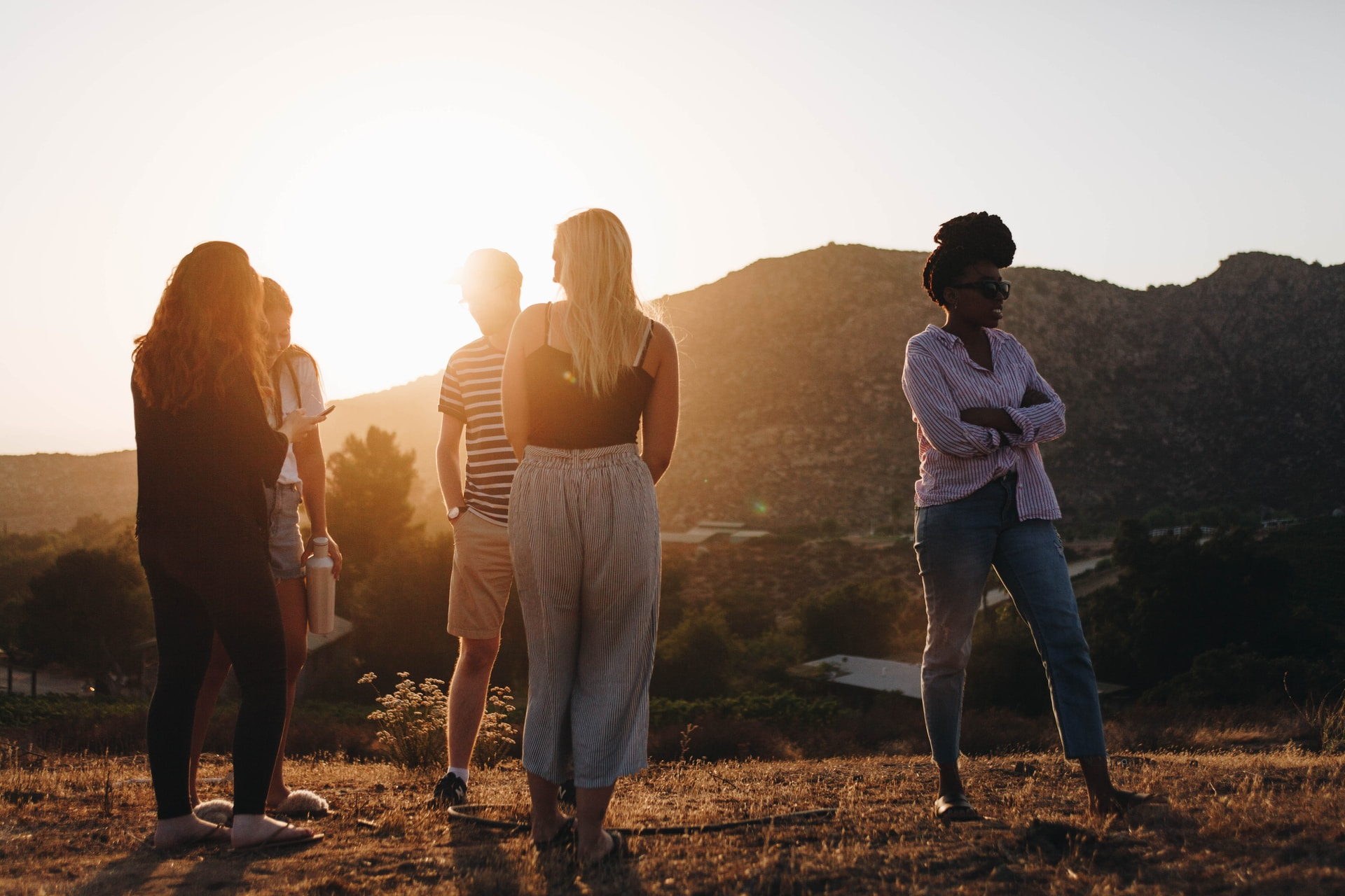 five person standing near mountain at golden hour