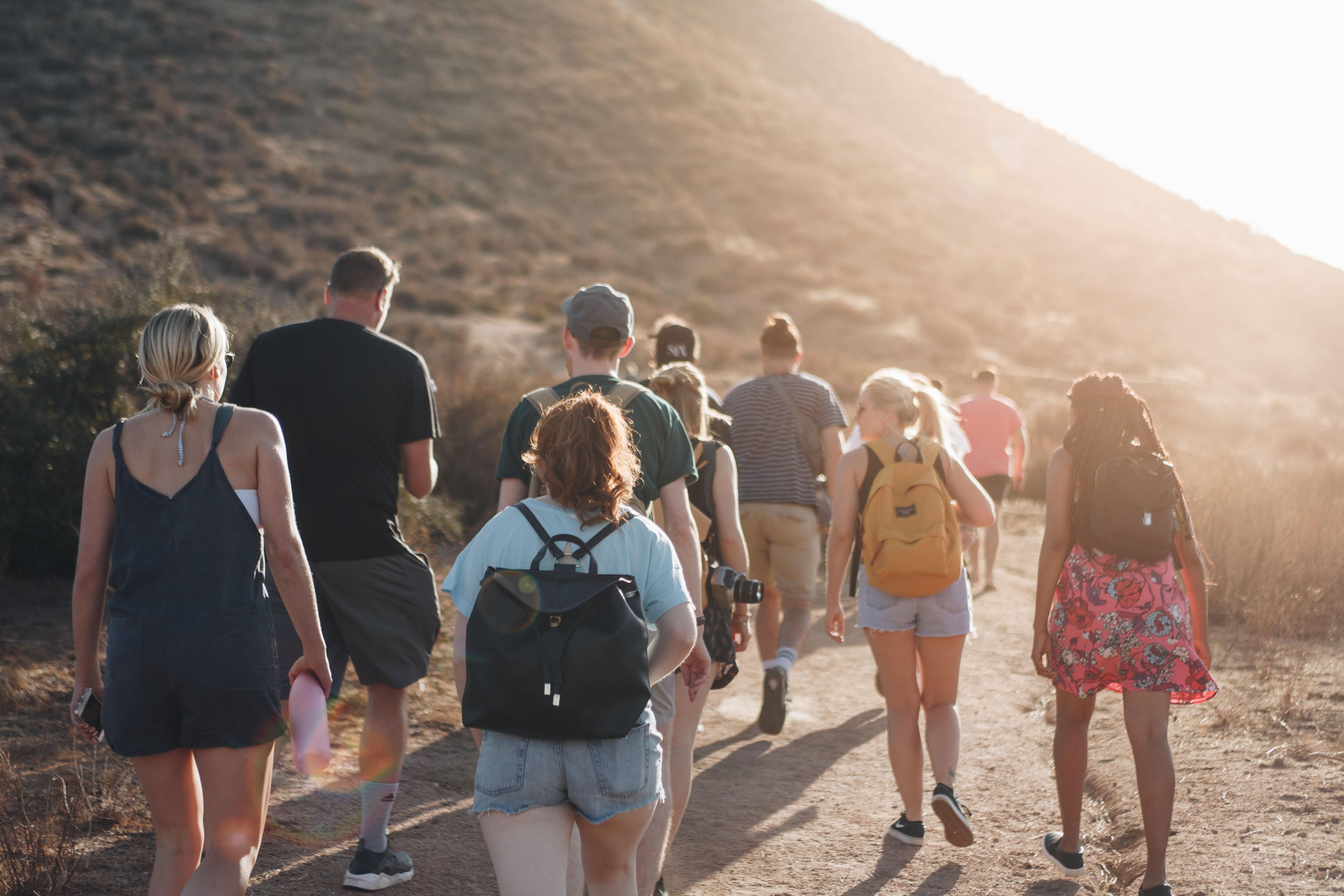 people walking on dirt road near mountain during daytime