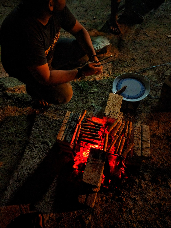 man sitting near grill