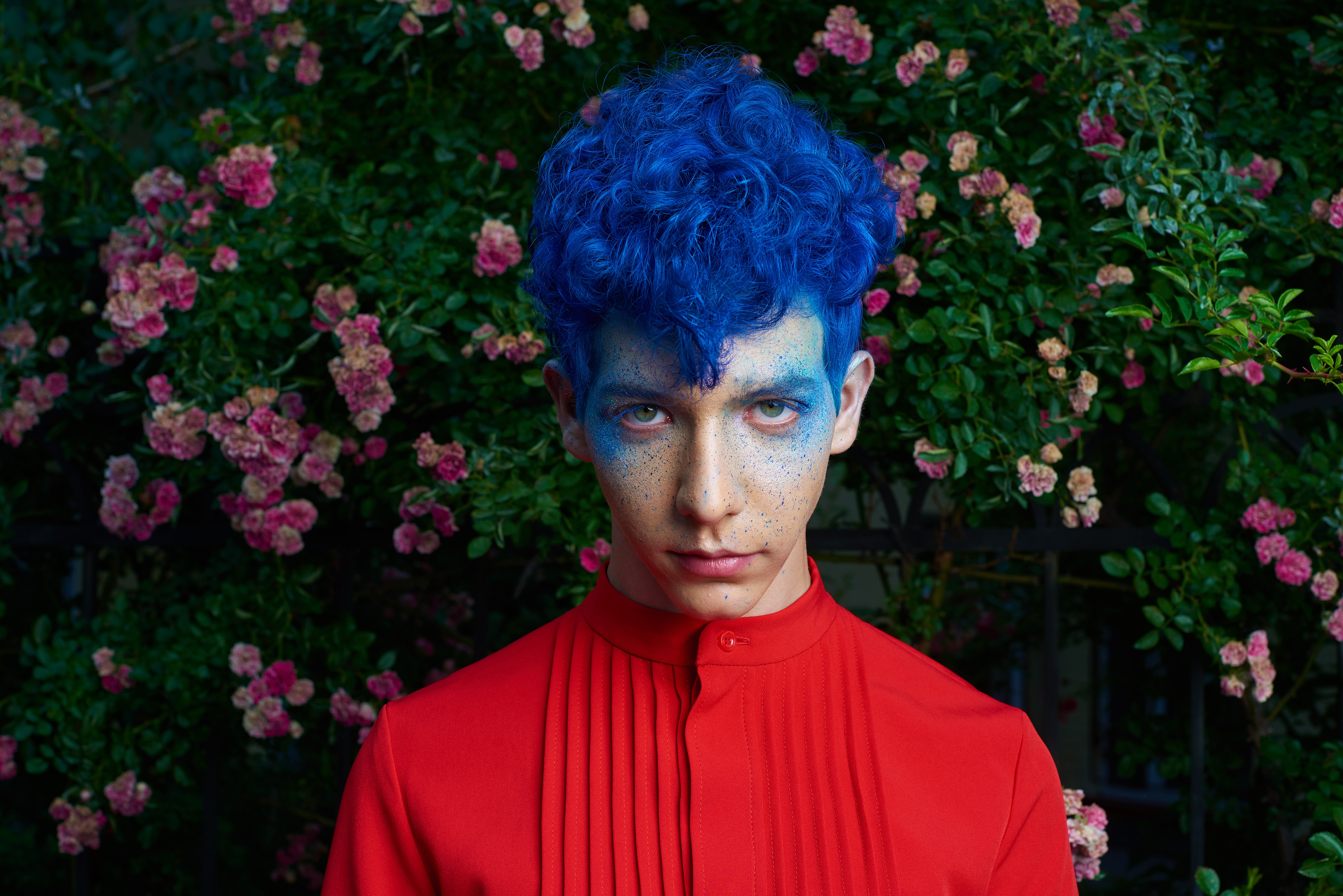 blue haired man standing in front of pink flower plants