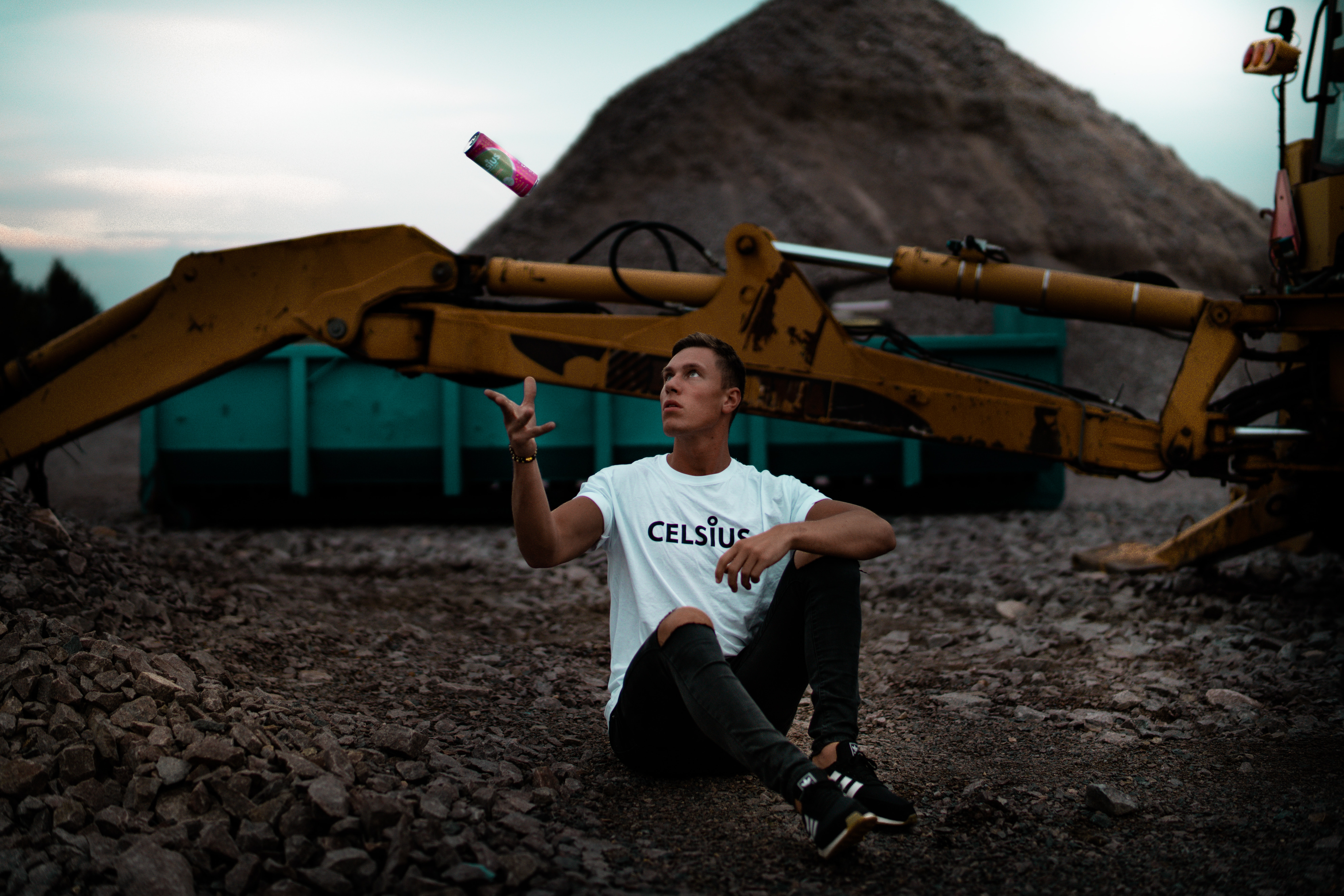 man sitting on the ground near excavator