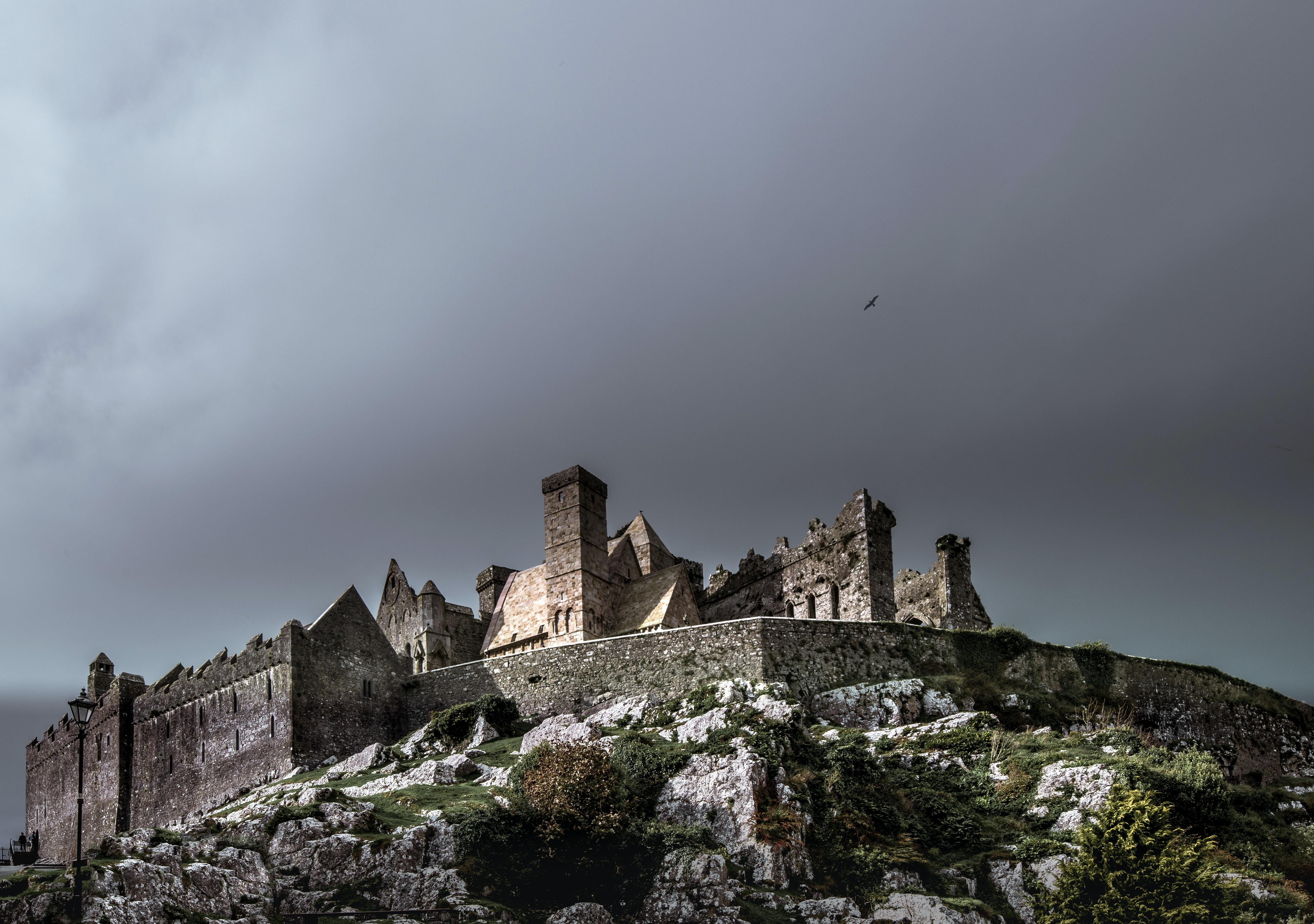 brown concrete castle under black clouds during daytime