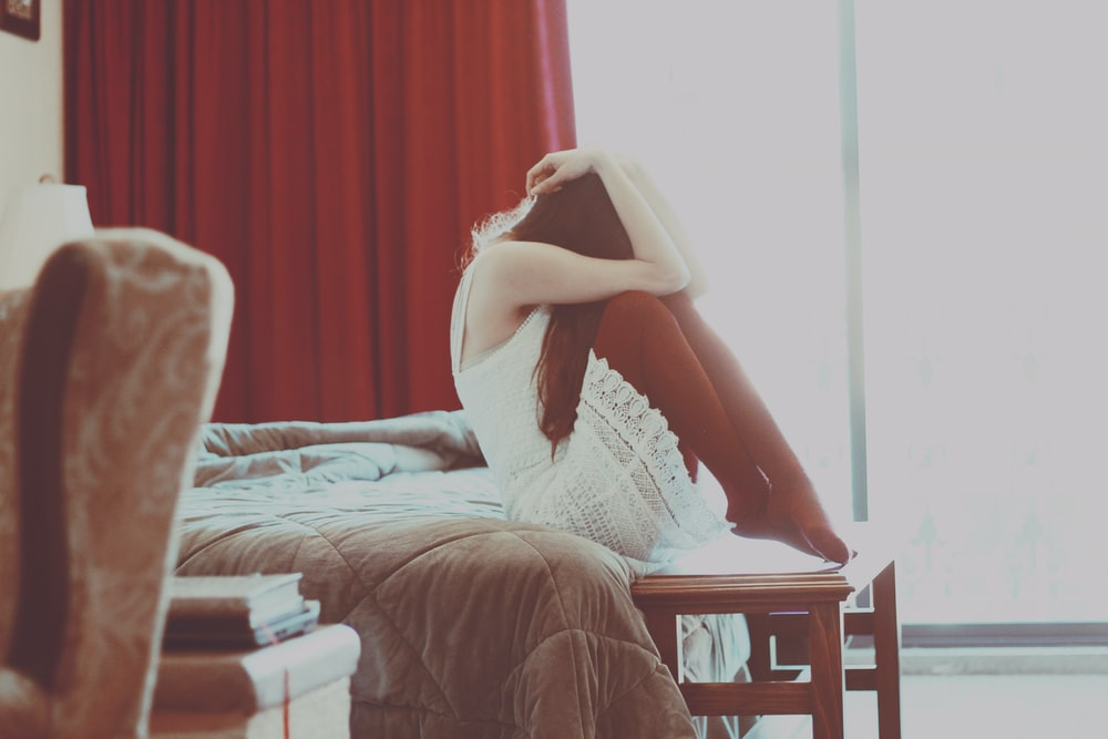 woman wearing white dress sitting on bed inside room