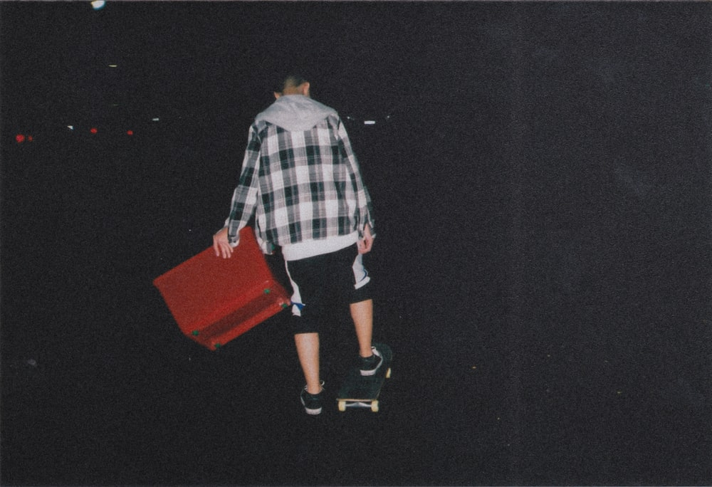 person putting his foot on skateboard