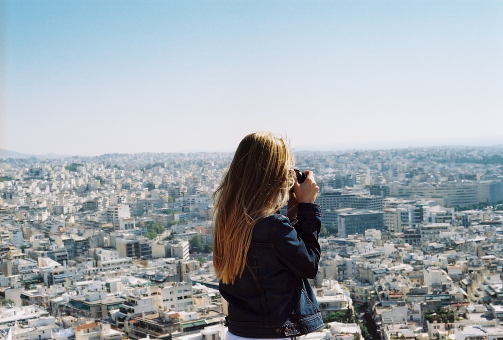 woman taking photo the city