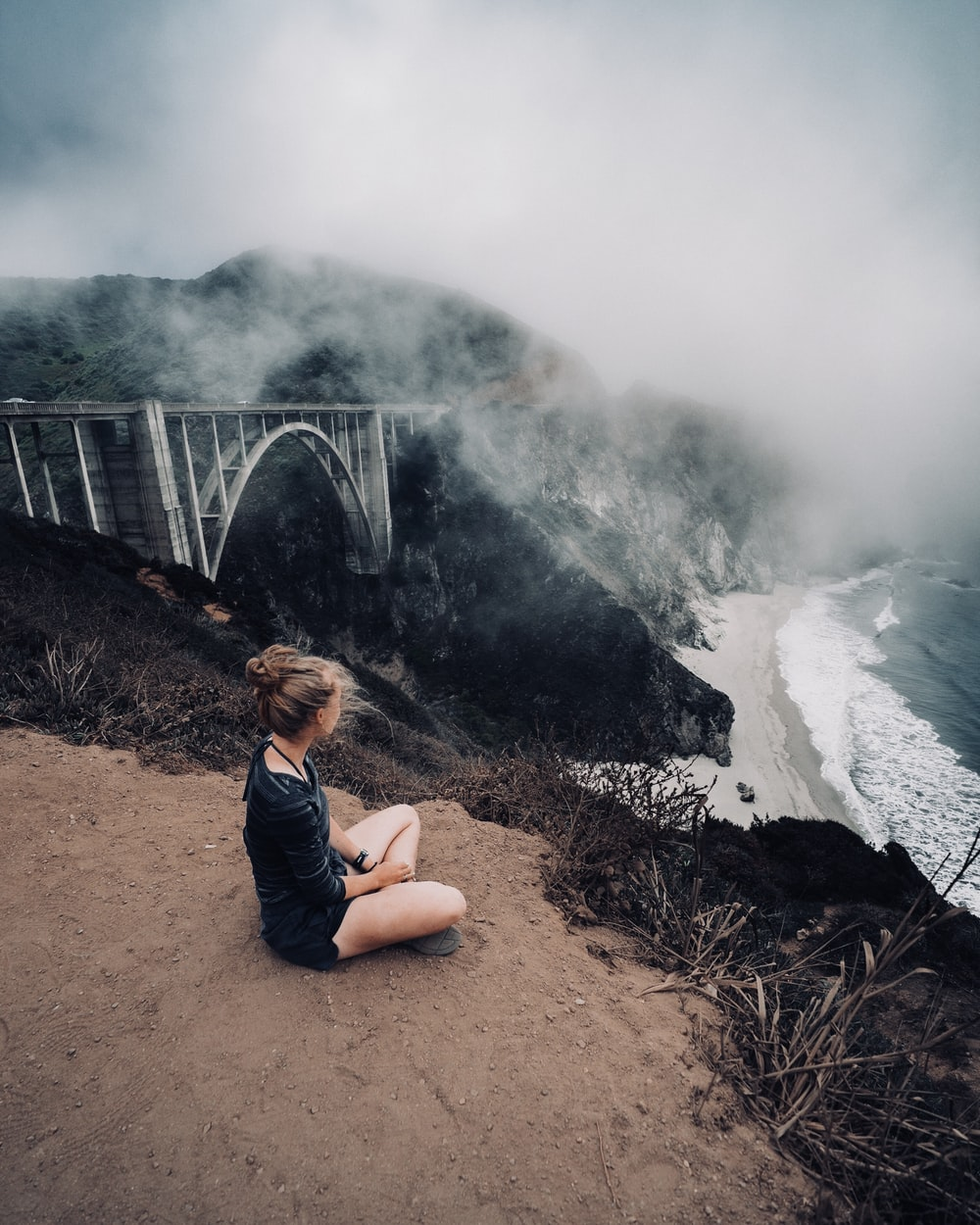 woman in black top sitting beside of mountain cliff during cloudy sky