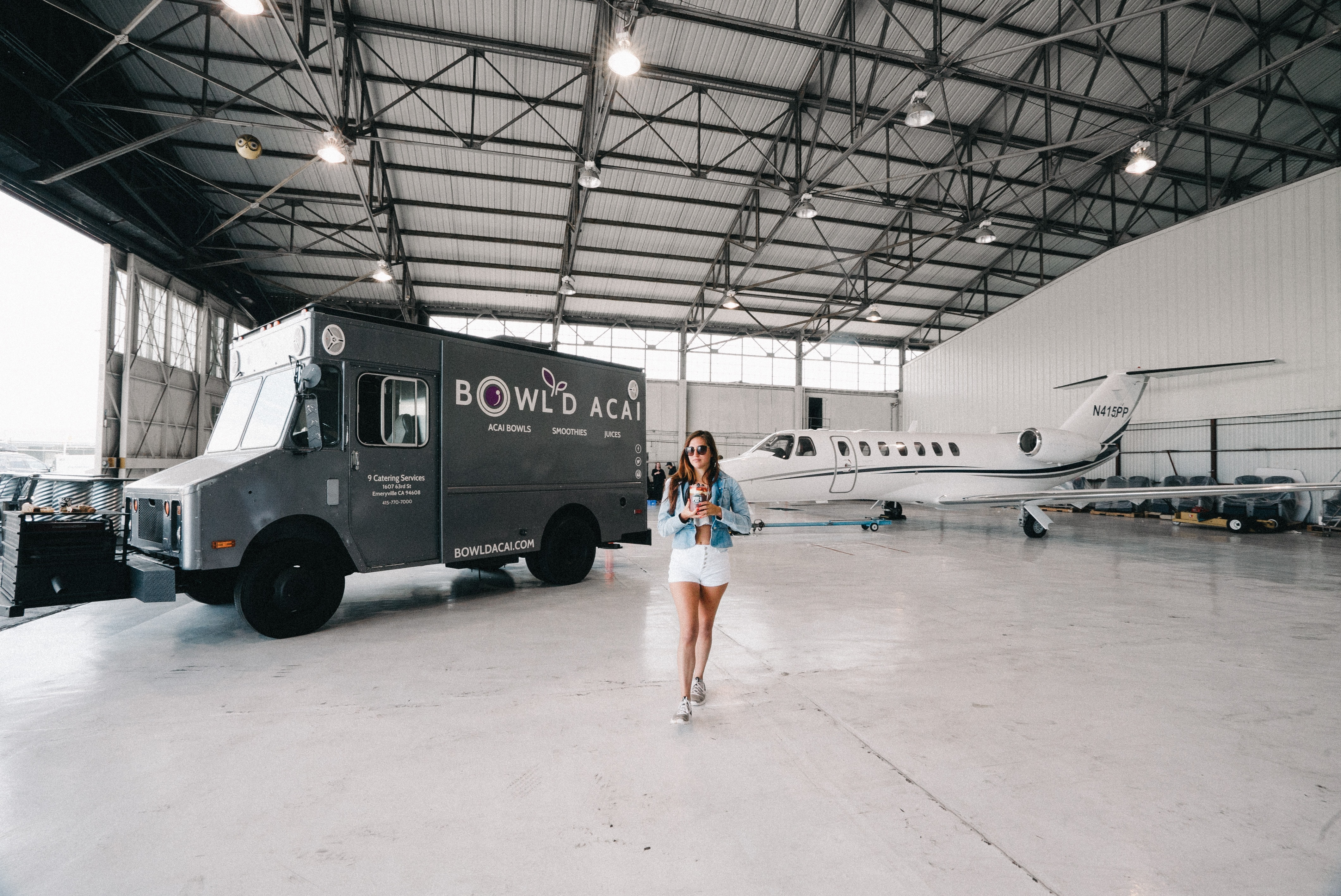 woman standing near white plane and vehicle