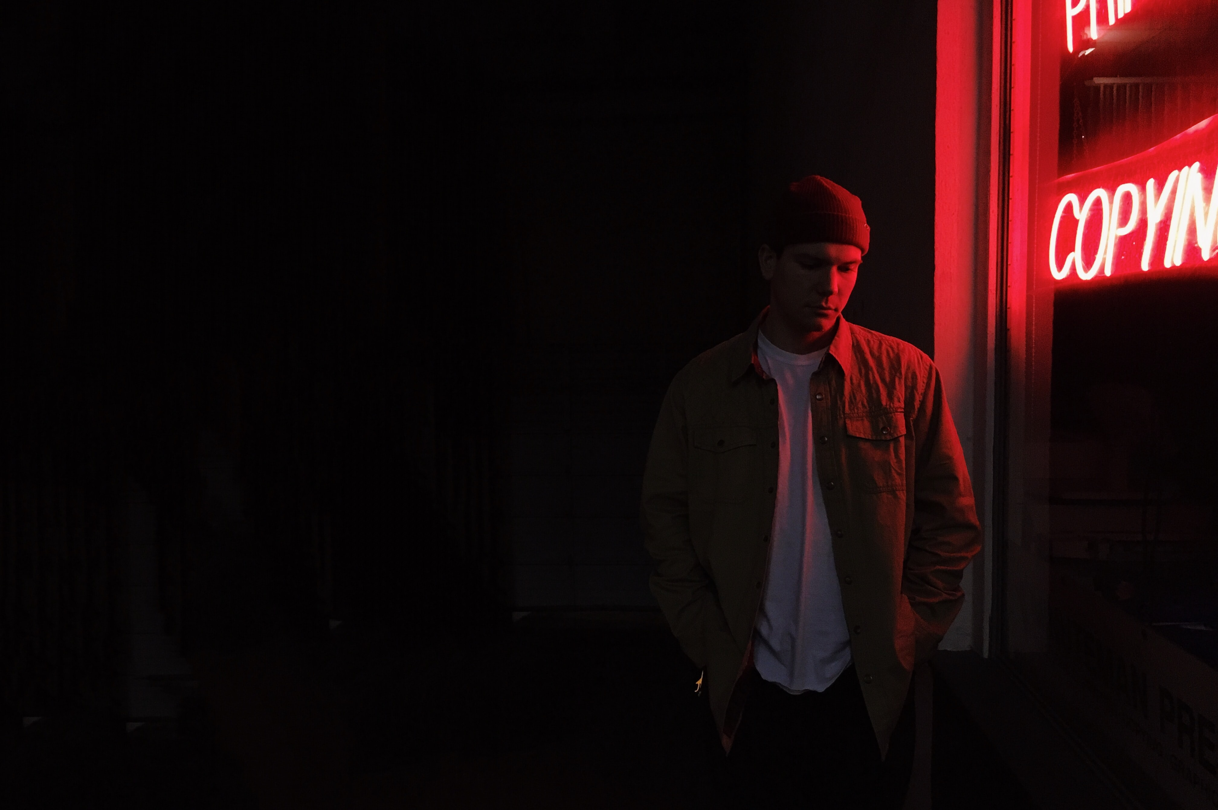 man standing near red neon sign