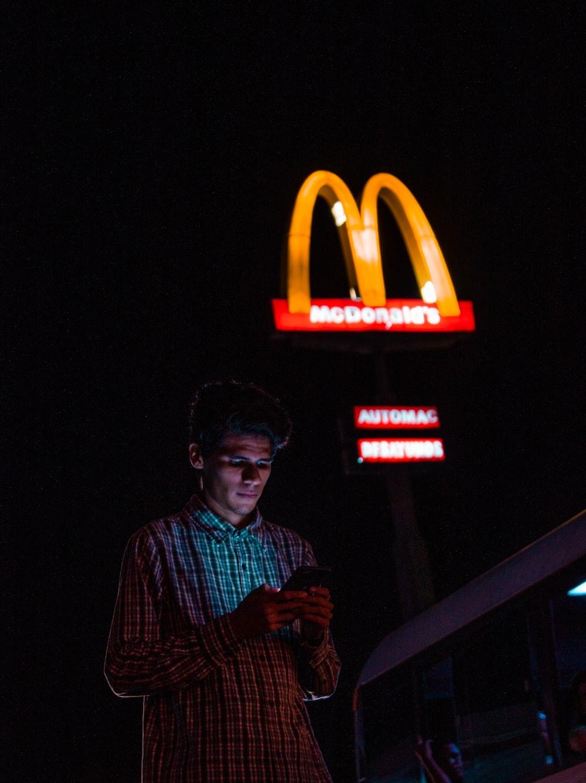 man using Android smartphone near McDonalds