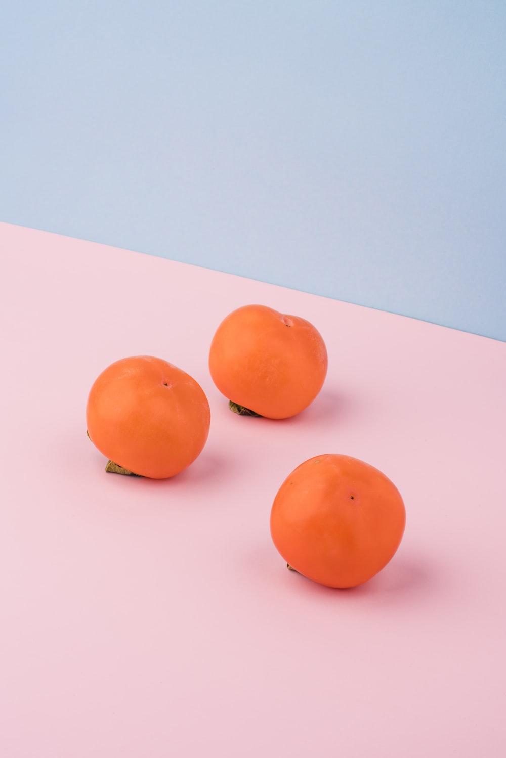 three orange fruits on pink surface