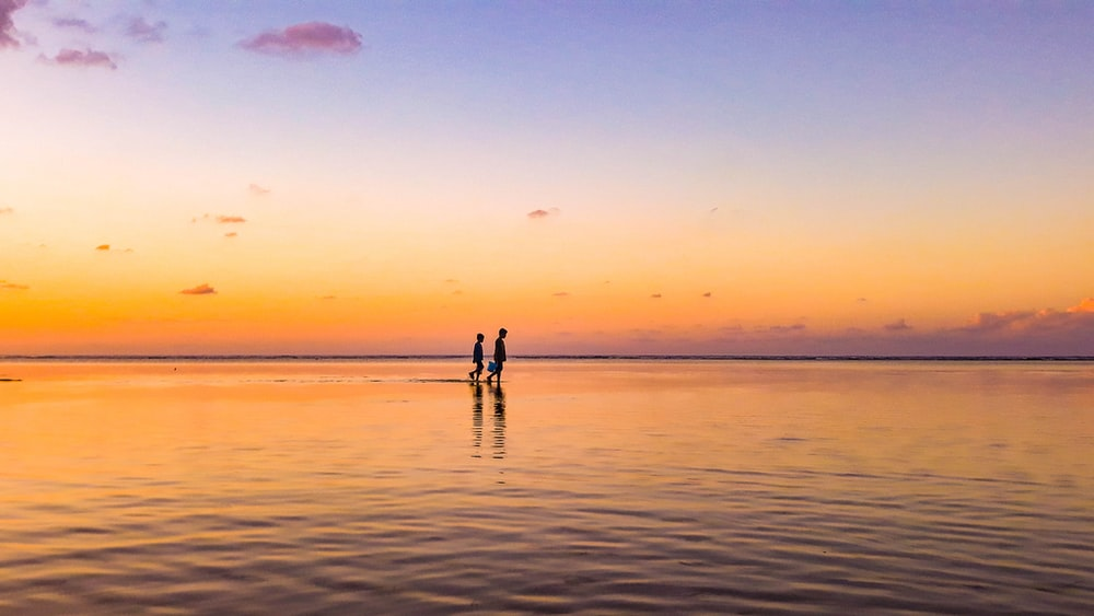 two person standing in sea