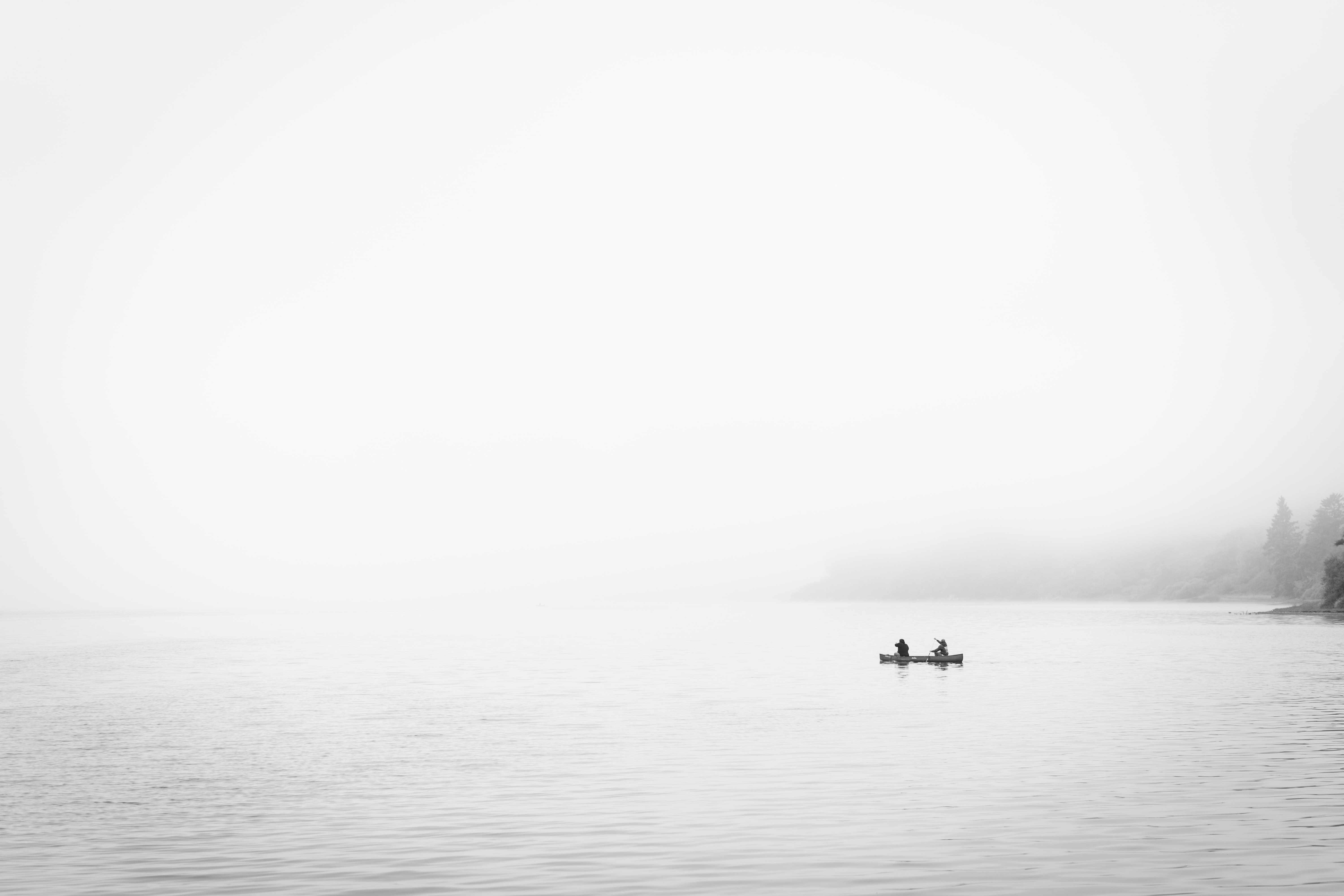two person in boat on body of water