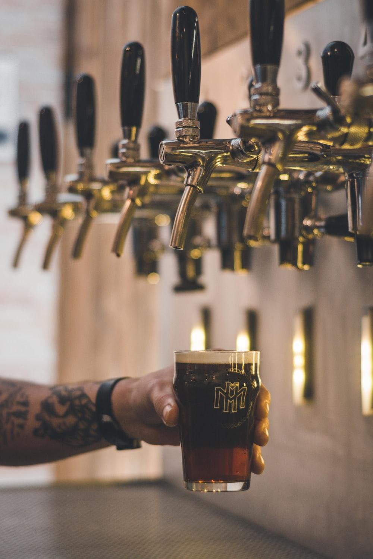 person holding beer mug under keg tap