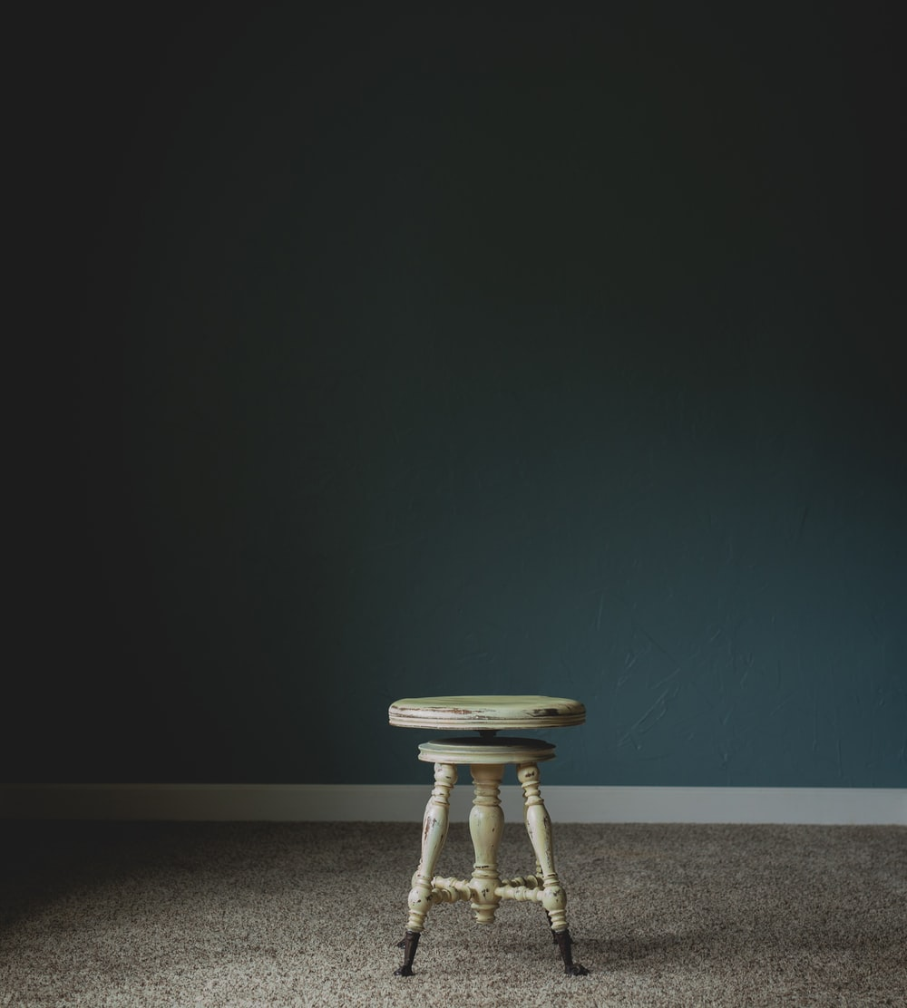 white wooden stool chair near wall