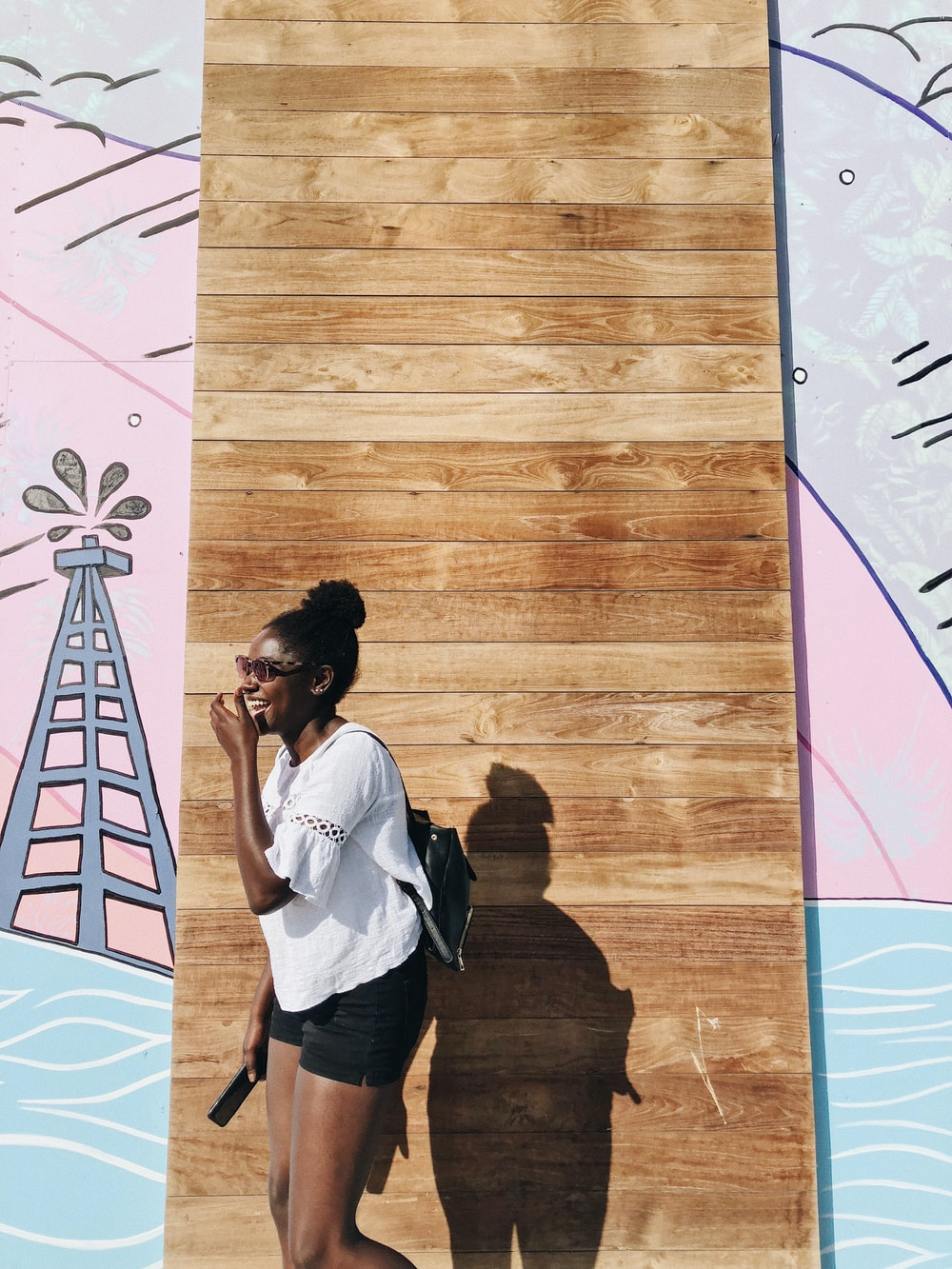 woman standing behind brown wall