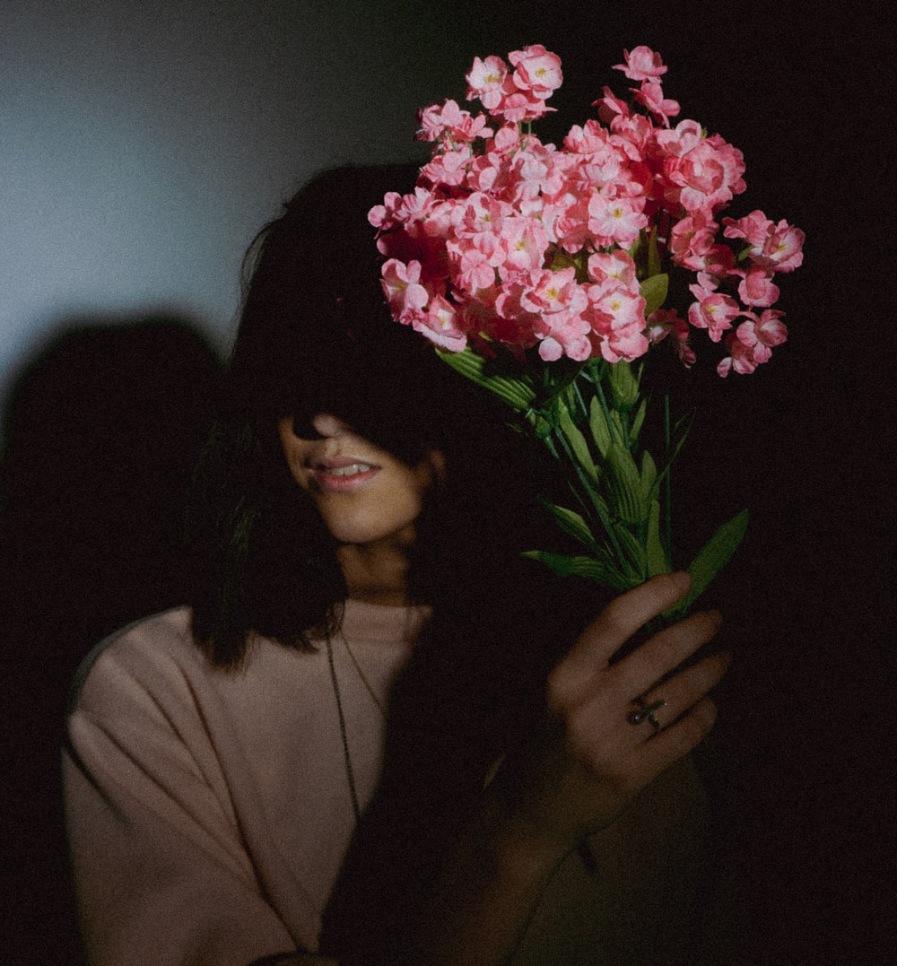 woman holding faux pink flower decors
