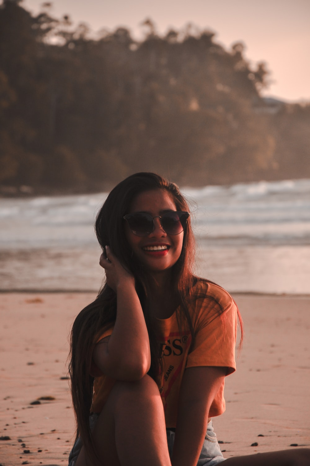 woman sitting on sand while smiling