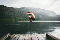 man jumping on body of water during daytime