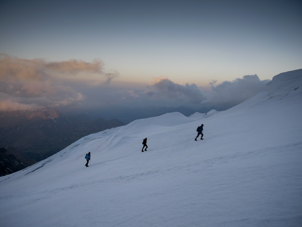 three person climbing on snow covered mountain
