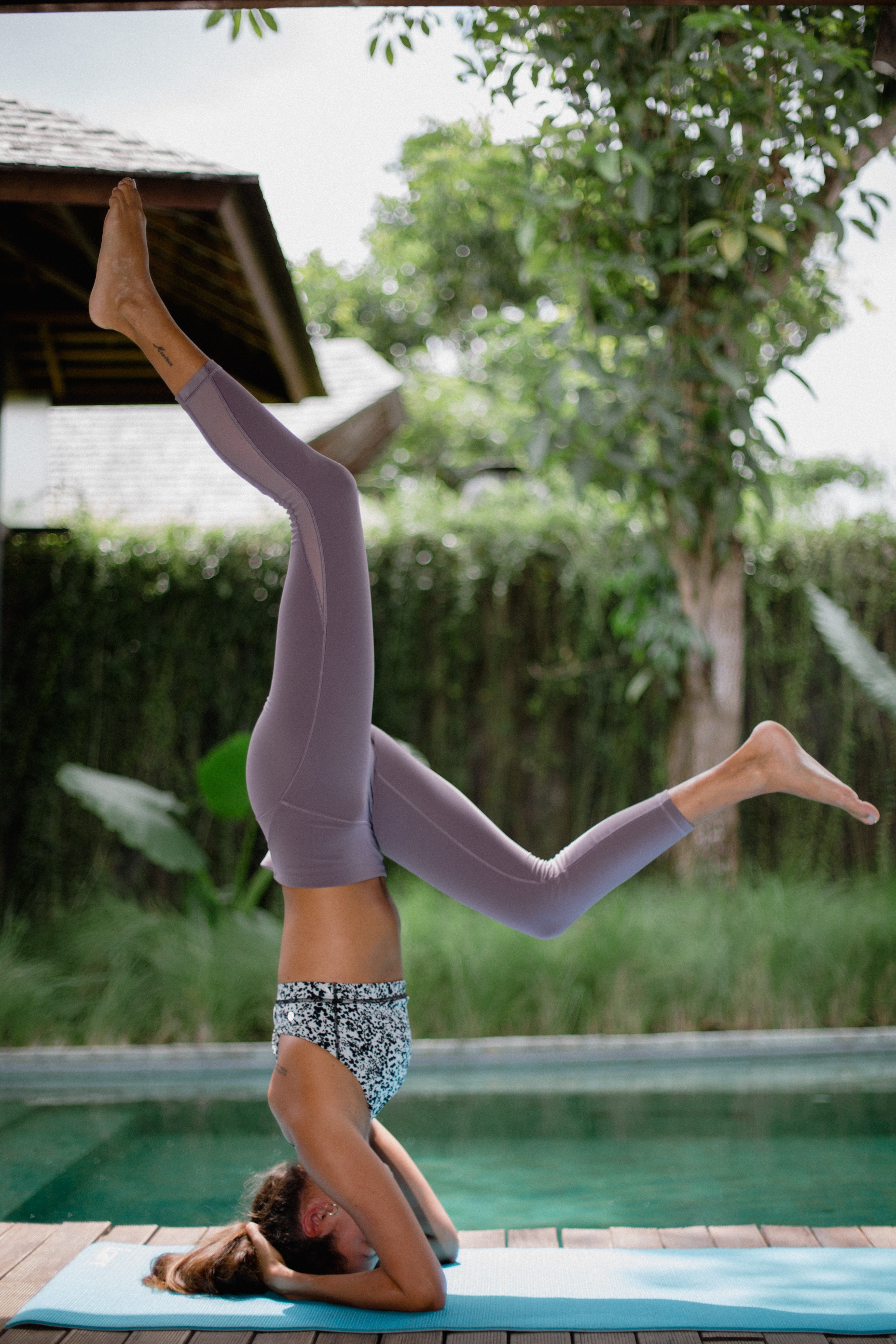 woman head standing on yoga mat with swimming pool background