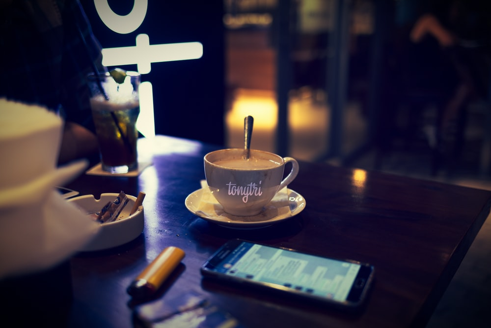 black Android smartphone beside teacup on brown wooden coffee table