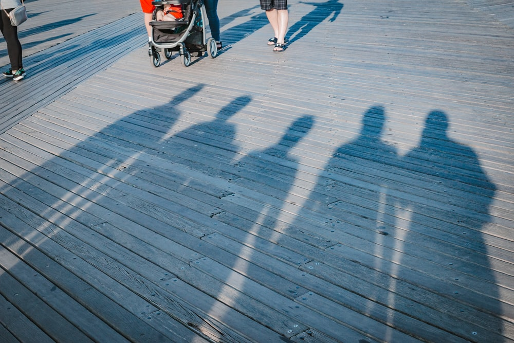 five people shadow near black stroller during daytime