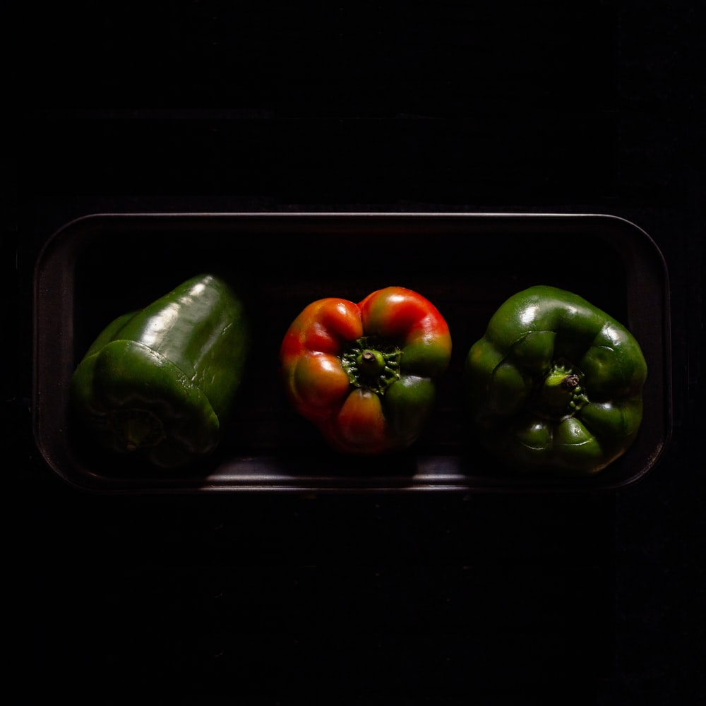 three orange and green bell peppers on black plate