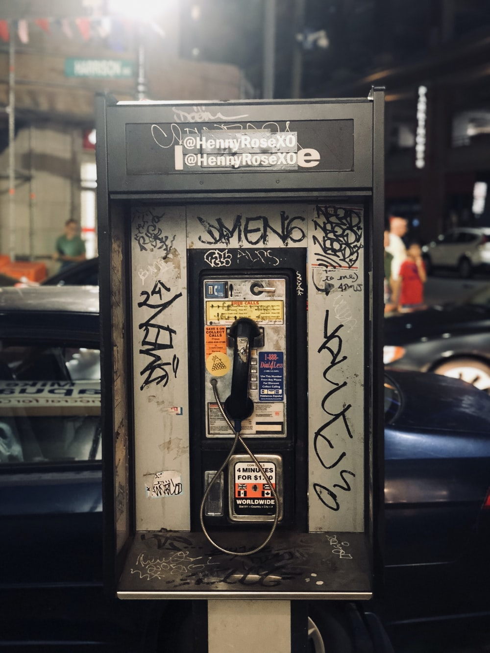 vintage rectangular black and grey telephone booth overlooking people in front of beige building