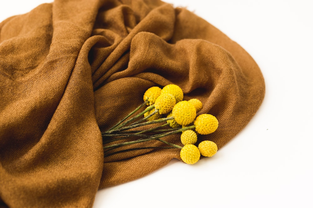 yellow flowers on brown textile