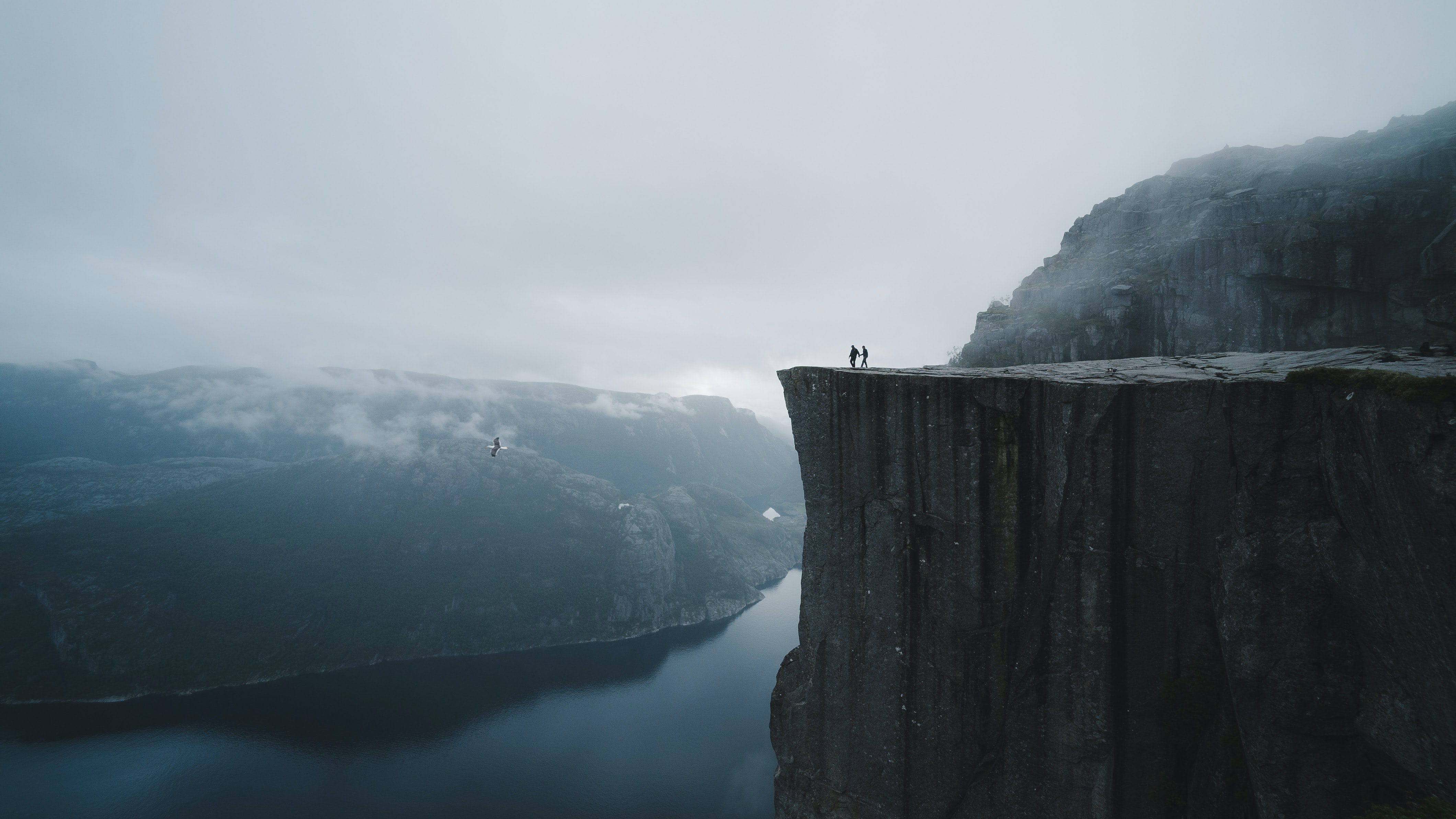 two people standing on edge of cliff at daytime