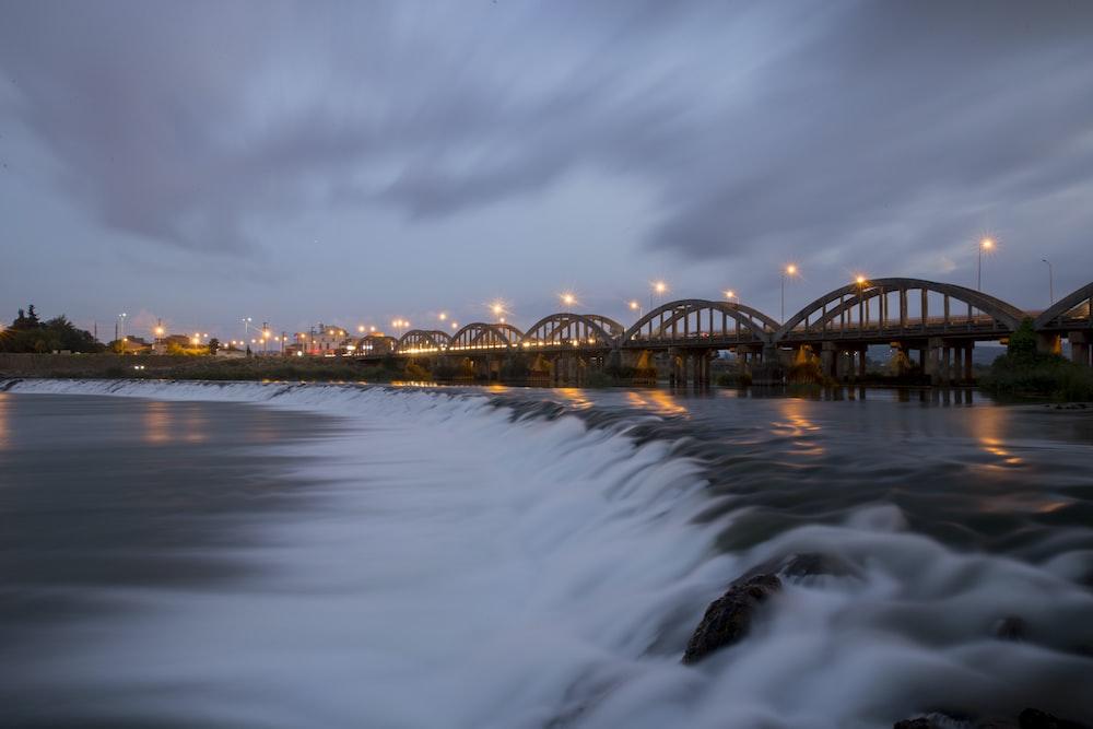 brown concrete bridge above body of water