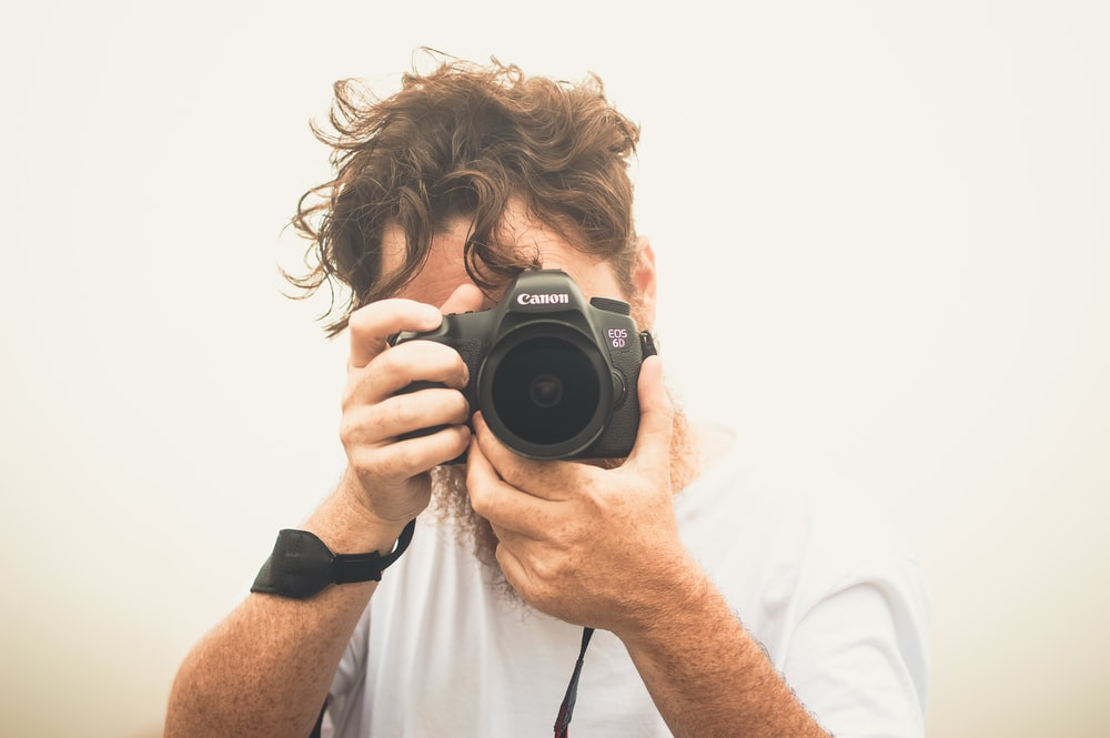 man taking pictures using Canon