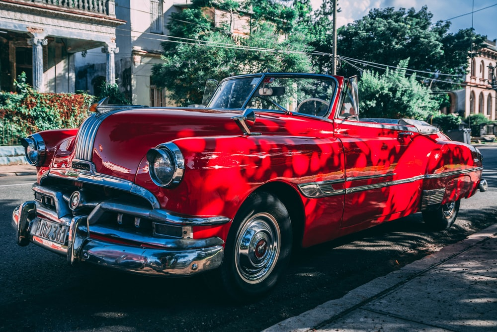 classic red convertible coupe parked beside road