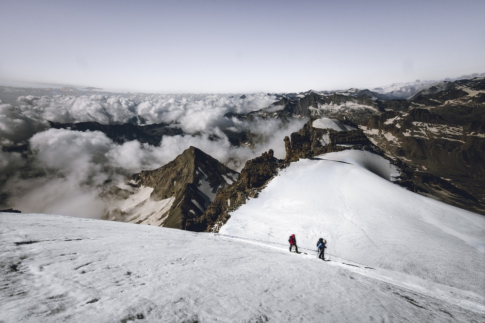 two person walking on snow covered mountain