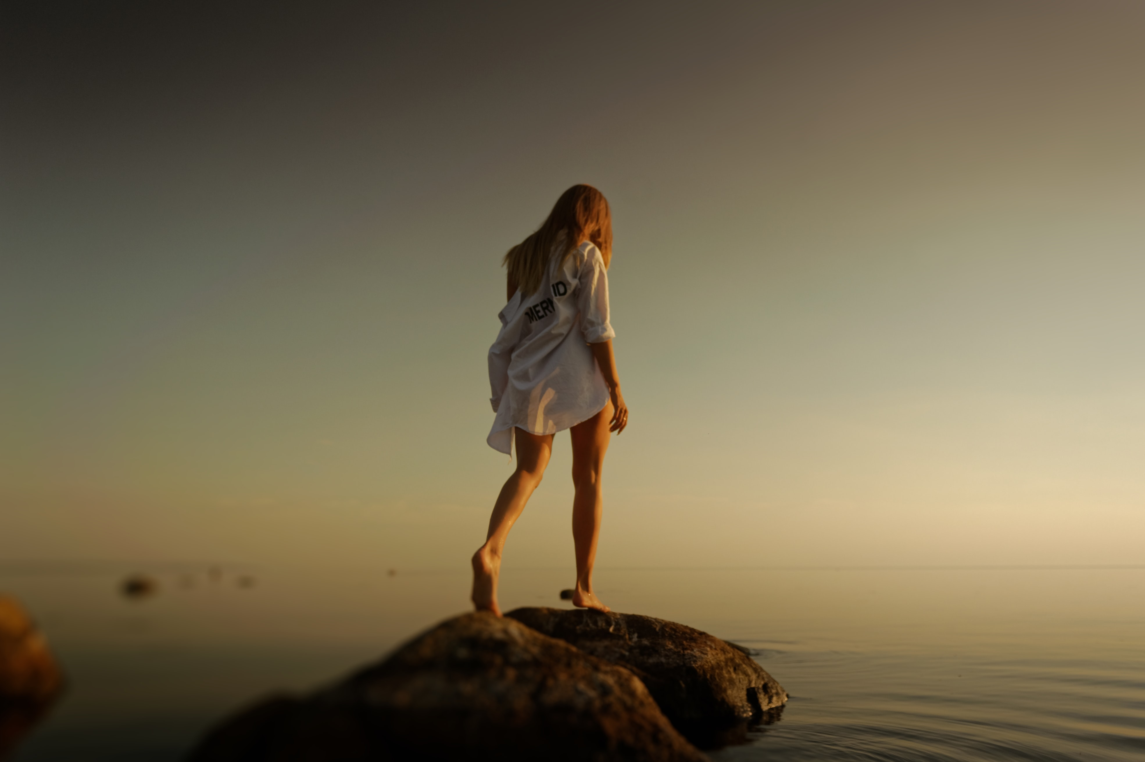 woman walking over brown rocks near body of water during daytime