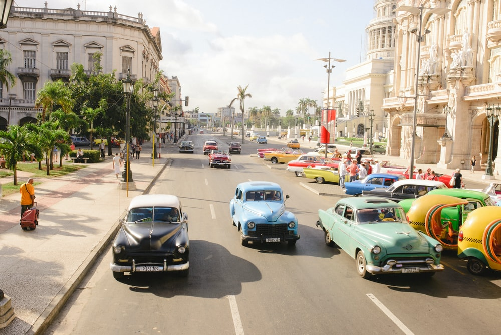 three assorted-colored vintage car on road