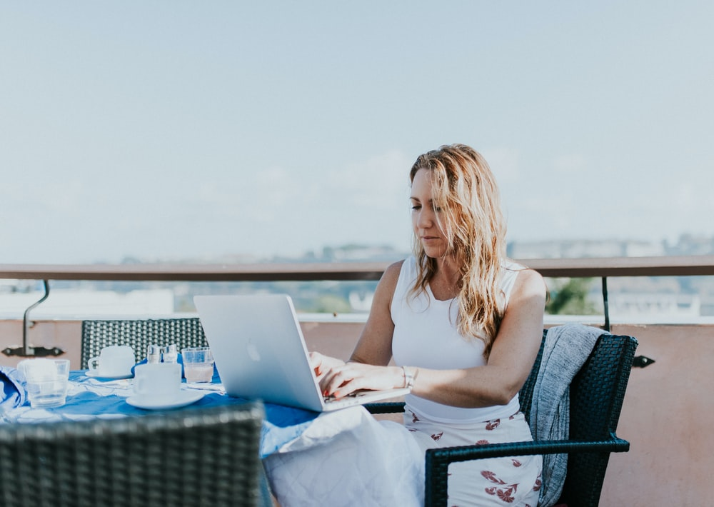 woman sitting on chair while using MacBook