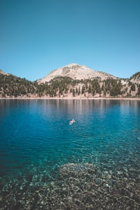 man floating on blue sea surrounded by mountain